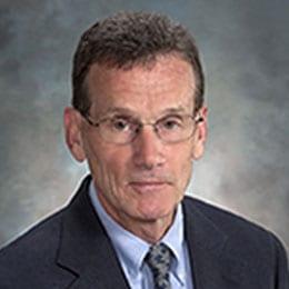 Headshot of Dr. Hoard wearing dark suit and necktie