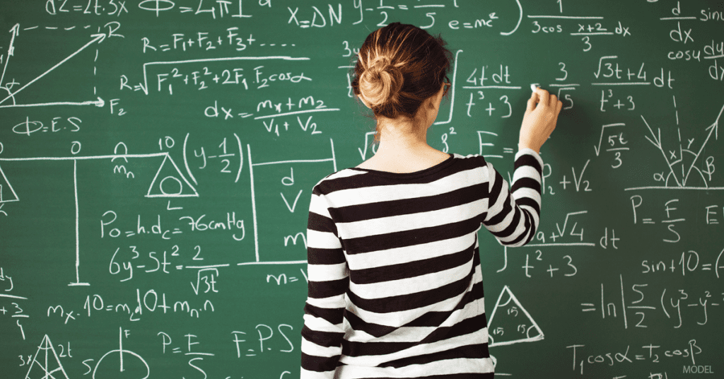 Woman wearing black and white striped shirt doing math calculations on a chalk board