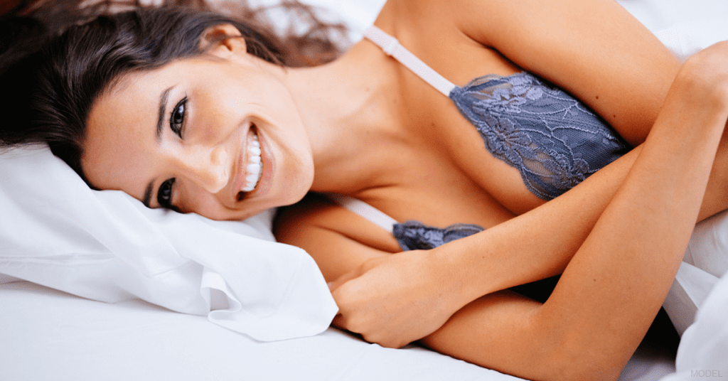 A woman rests after a full recovery from breast augmentation surgery.