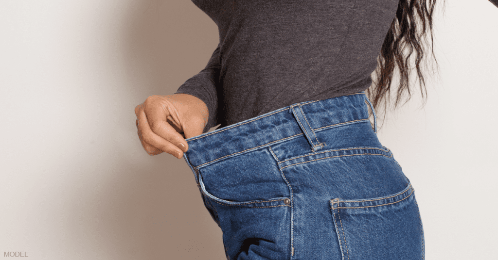 A woman holds out the loose waist of blue jeans following a liposuction procedure