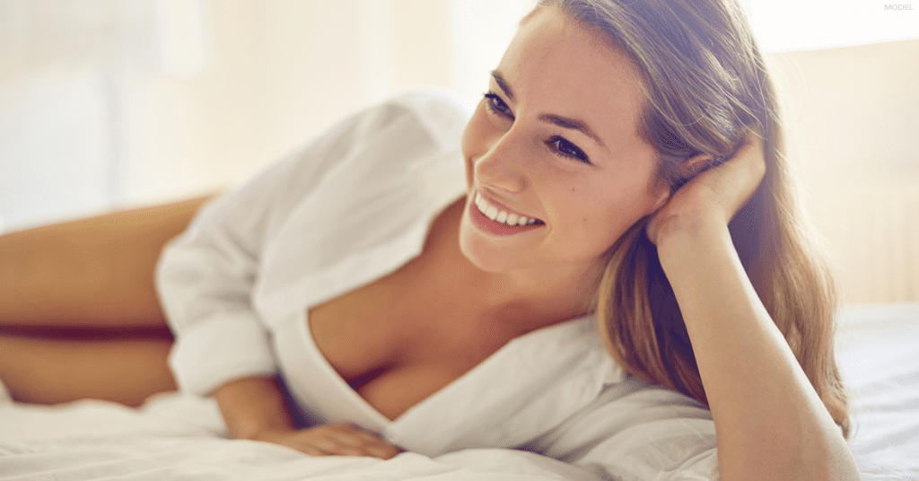 A woman considering breast enhancement rests on a bed and wonders if breast implants or a breast lift is right for her.