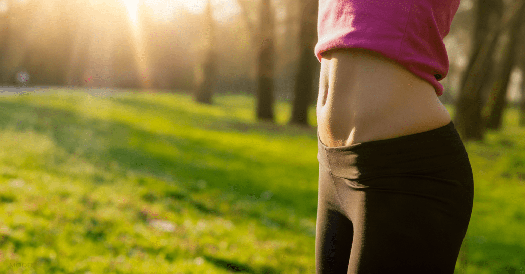Torso of a woman wearing black yoga pants standing in grass with toned abdomen exposed