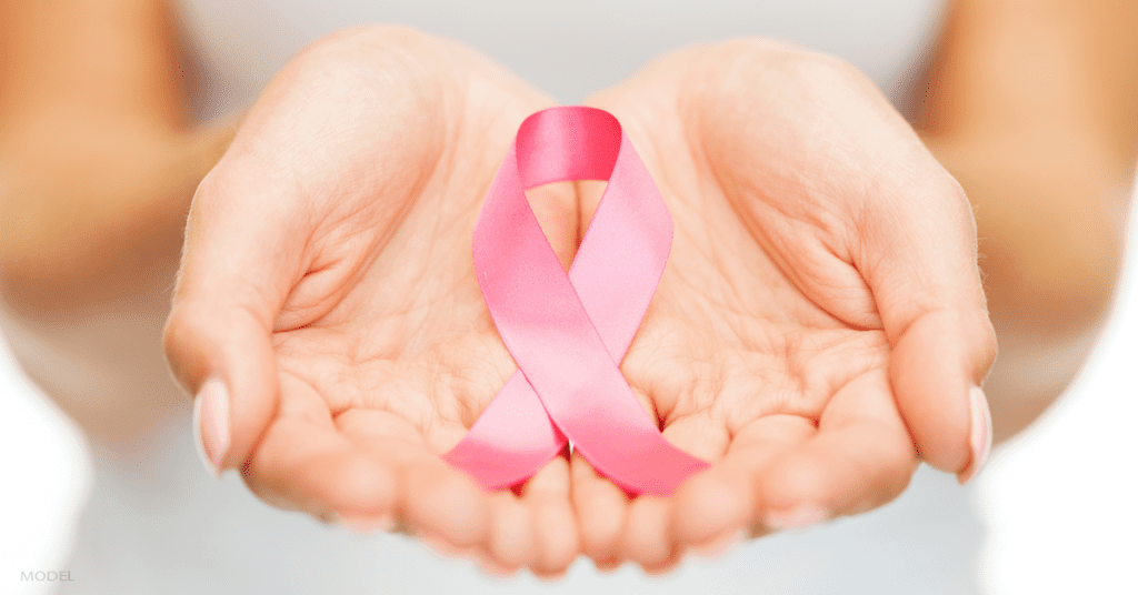 A woman holds a pink ribbon that represents breast cancer awareness.